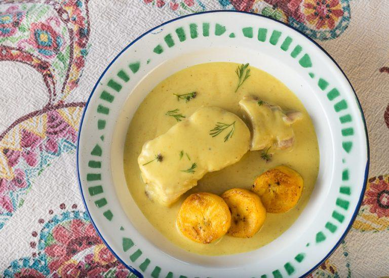 Un plato de loza blanco con detalles verdes sobre mantel estampado con colores, contiene un pedazo de pesca blanca cubierto de salsa de encocado y decorado con tres plátanos maduros.