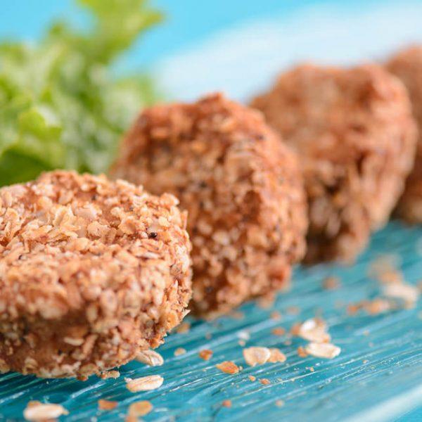 cinco apetitosos nuggets circulares naturales de pollo, colocados uno tras otro, con apanadura de cereales, sobre plato de vidrio con fondo turquesa, atrás vemos lechugas.