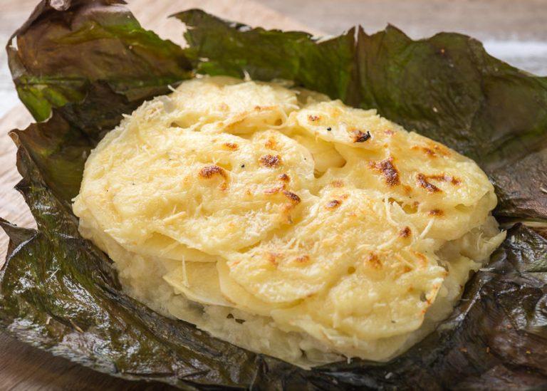 Deliciosa porción de gratín de láminas de zanahoria blanca con queso mozarella, gratinado sobre hoja de achira en la que fúe envuelto para su preparación