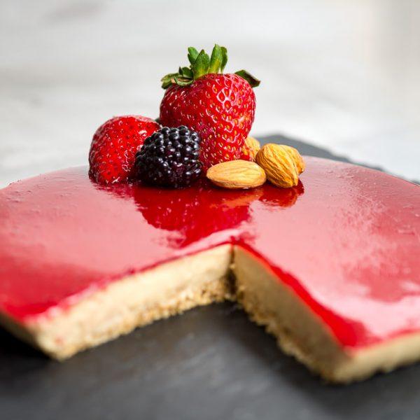 Un cheesecake de ricotta y frutos rojos, decorado por una fresa partida en la mitad, una mora y tres almendras.