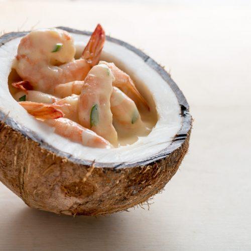 Unos jugosos camarones con salsa de encocado servidos sobre medio coco maduro
