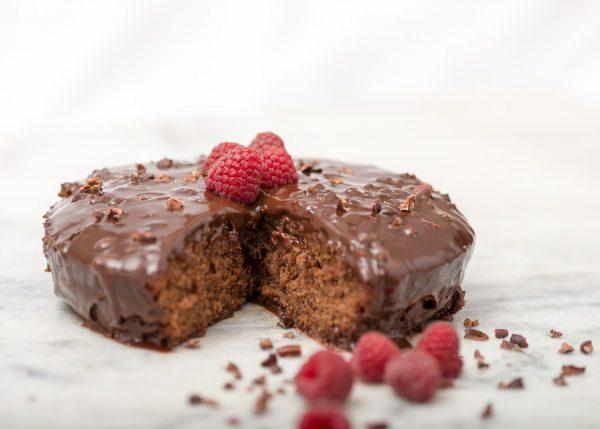 Pastel de chocolate redondo, con fudge de chocolate encima y decorado con nibs de cacao y 4 frambuesas frescas. Vista lateral del pastel de chocolate en la que se ha cortado un pedazo de forma triangular. Sobre la base de marmol hay mas frambuesas y nibs de cacao